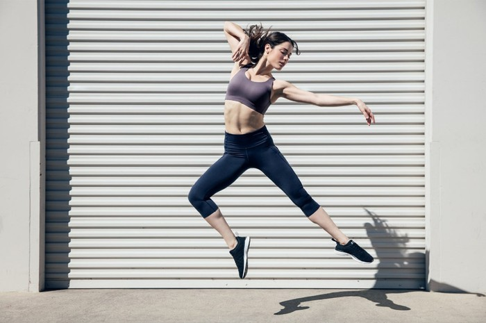 Woman wearing Lululemon's Enlite sports bra leaping into the air like a ballerina.