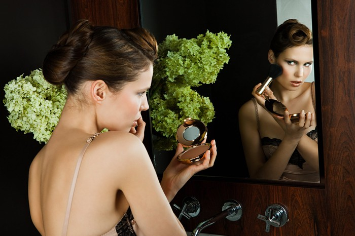 Young woman applying blush in mirror.