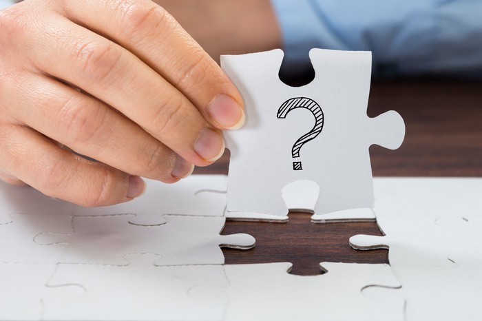 Hand holding jigsaw puzzle piece with a question mark on it over a jigsaw puzzle