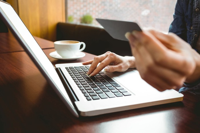 A woman holding a credit card in her left hand while her right hand is on the keyboard of her laptop. There is a cup of coffee on the table.