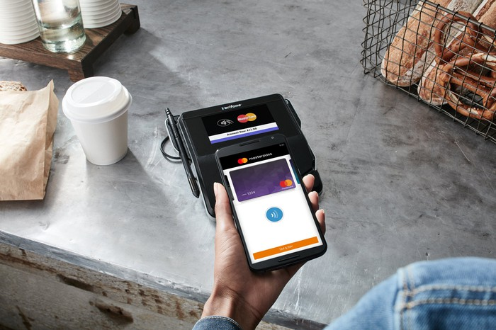 Person holding phone above payment terminal on counter. Phone displays MasterPass app.