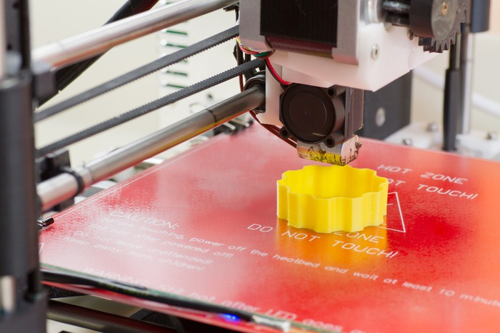 Printing a yellow 3D part with a small 3D printer.