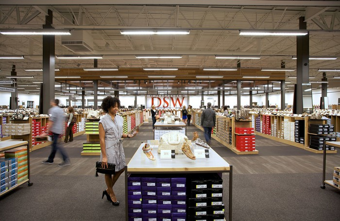 DSW store interior with multiple shoppers browsing the shelves