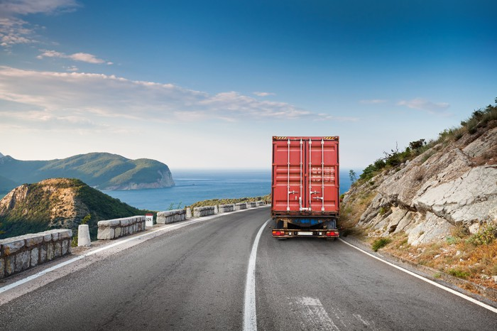 View of the back of a red truck traveling on a two-lane highway with mountain on one side and a body of water on other side.