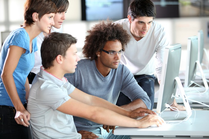 Young people cluster around a computer monitor