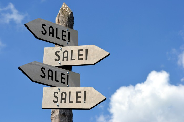 "A wooden post with four signs that say ""Sale!"""