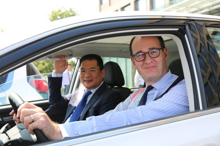 Jin Zheyong and Peter Fleet are shown inside a white car.