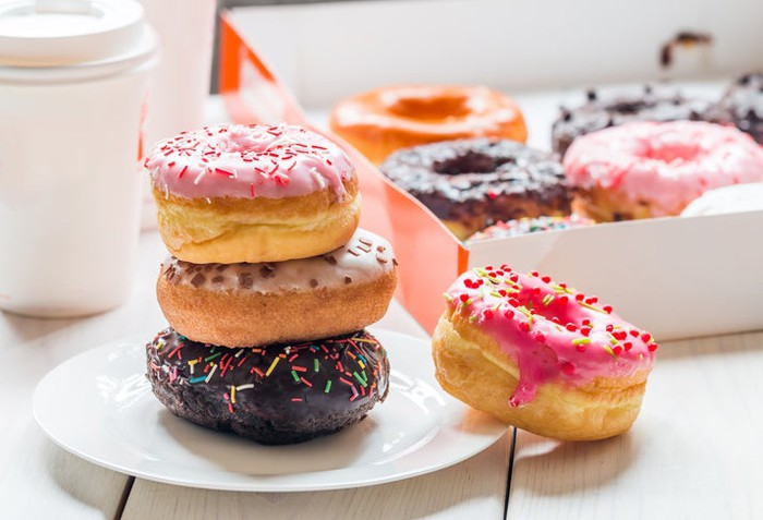 Colorful display of doughnuts, doughnuts box, and coffee resembling Dunkin' Donuts food and packaging.