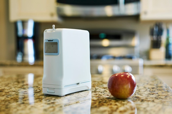 Inogen G4 next to apple on a table.