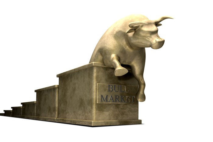 "A golden bull climbing up a golden set of stairs. On the front of the stairs is a golden sign, reading ""Bull Market."""
