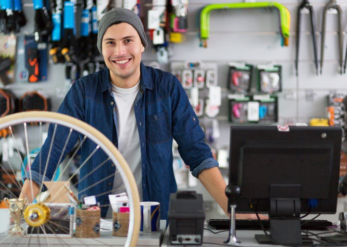 Smiling man standing behind the counter in a bicycle shop.