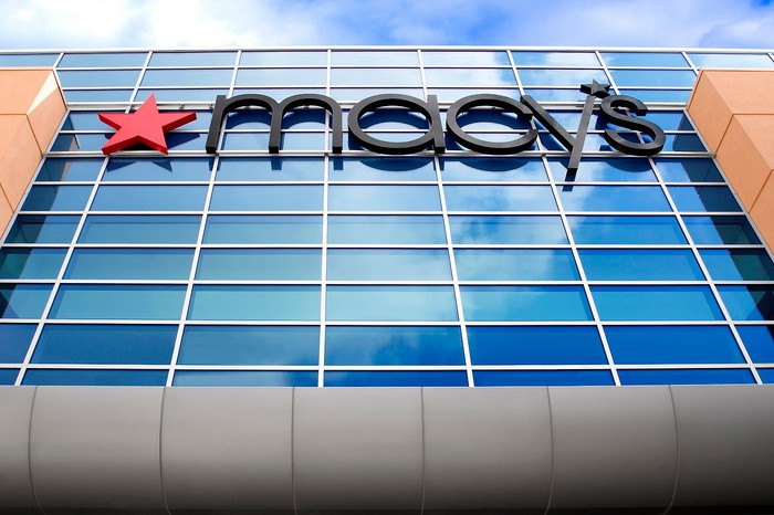 Macy's store front sign with a red star and blue window pane background