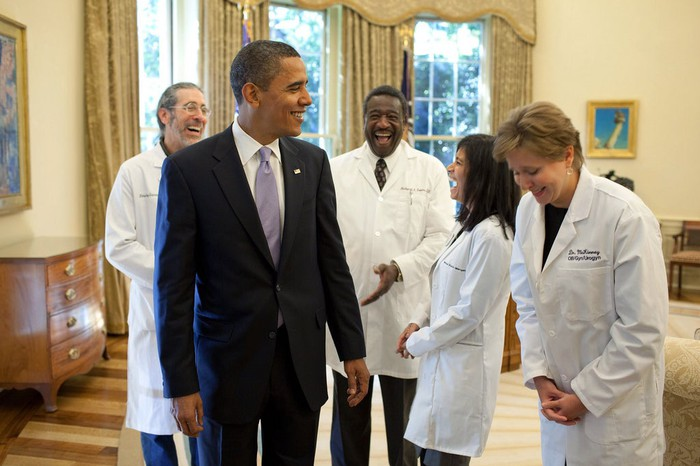 Former President Barack Obama laughing with doctors in the White House.