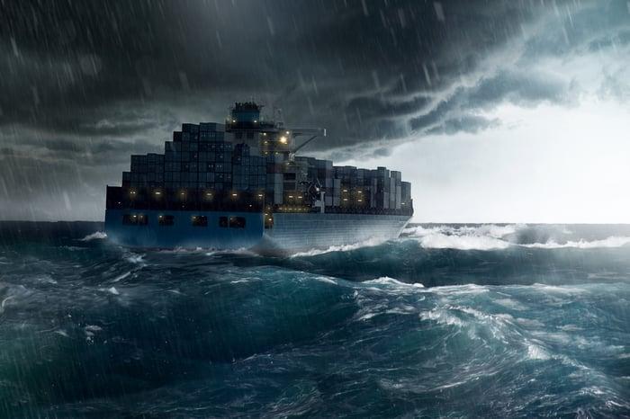 A container ship heading through a storm.