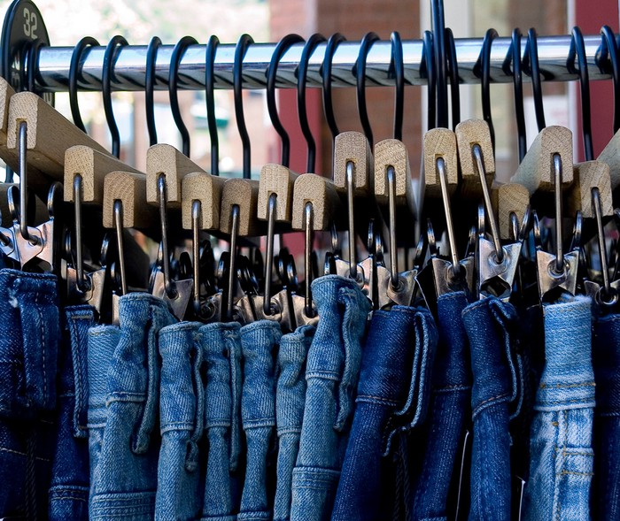Blue jeans hanging neatly on a store rack