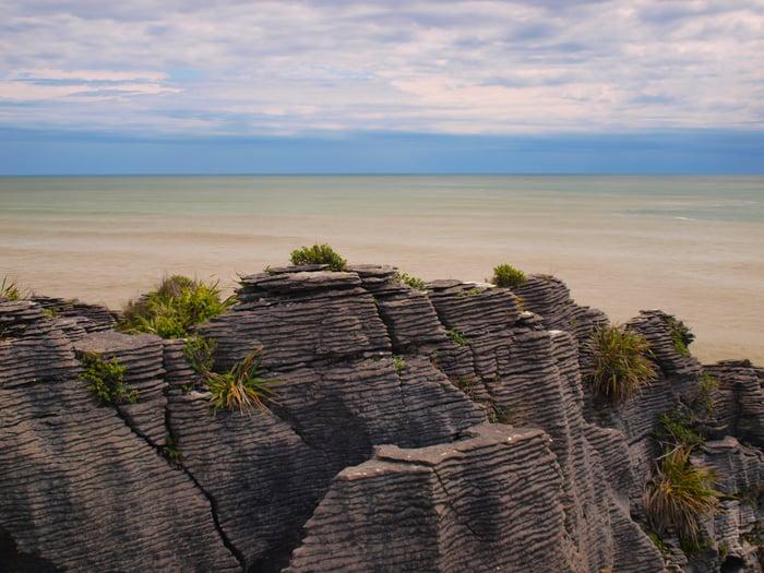 A mountain overlooks sand