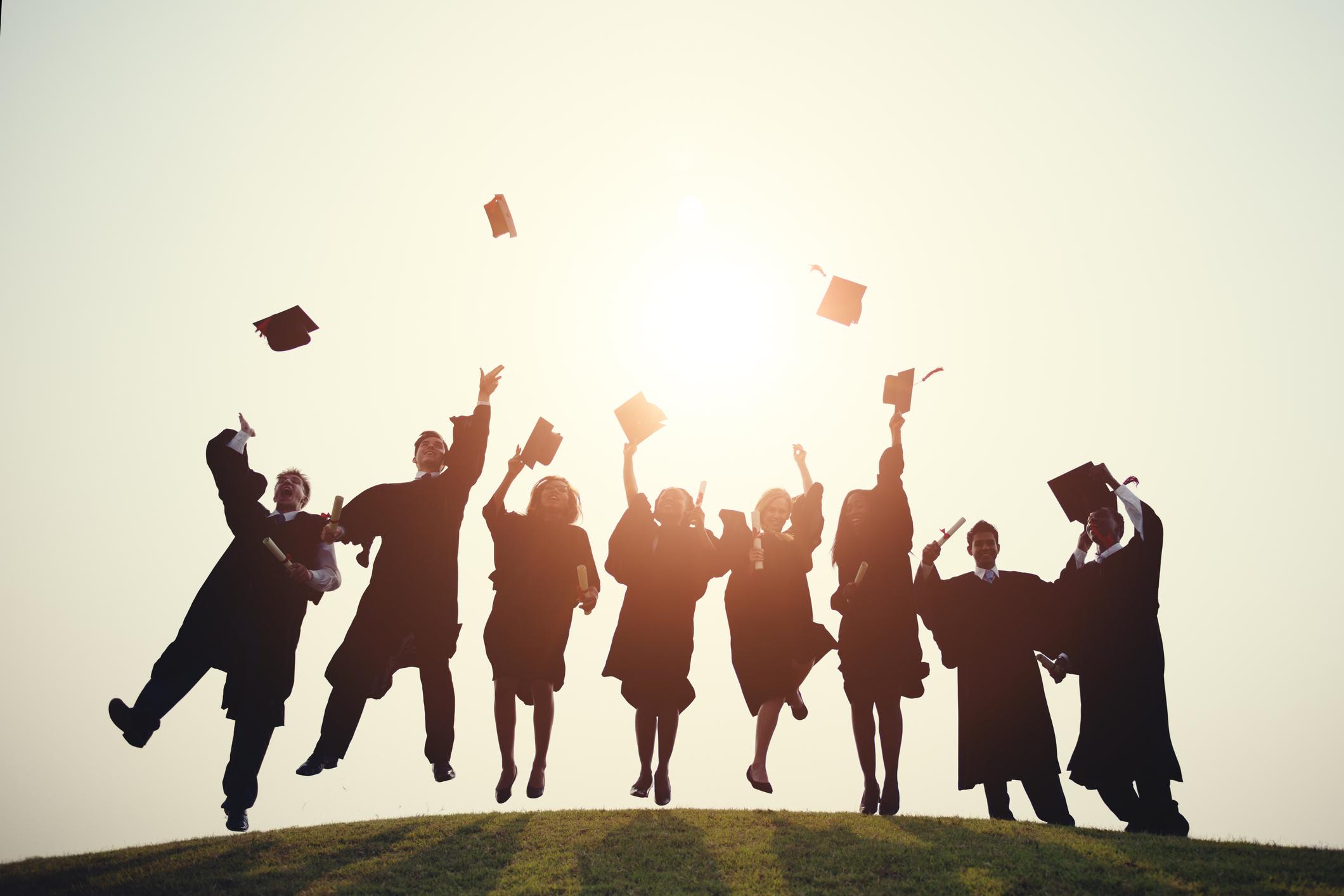 Graduates throw their caps in the air.