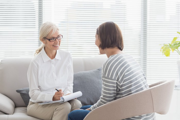A smiling therapist with a patient