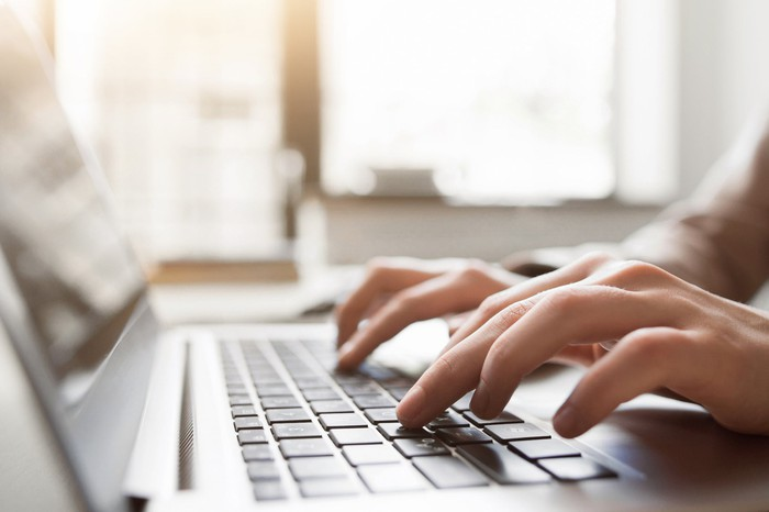 A person types at a laptop.
