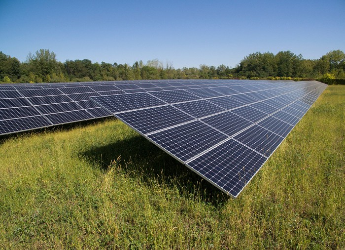 Utility scale solar system in a grassy field with trees in the background.