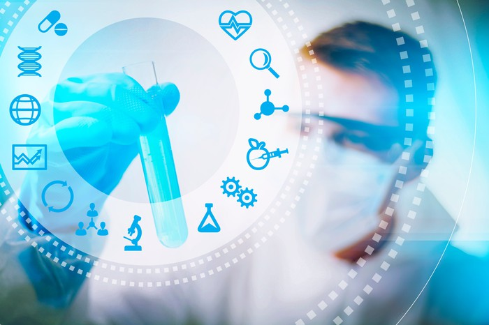 Biotech and scientific icons in foreground, with man wearing mask holding test tube in background