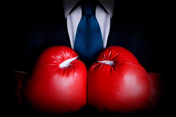 A businessman wearing big red boxing gloves.