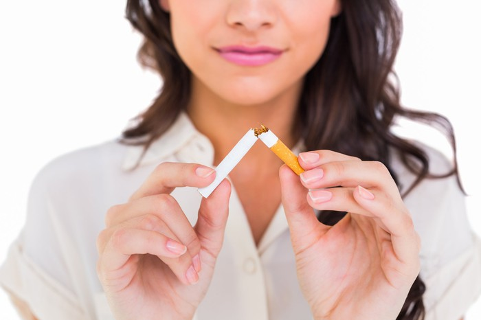 Person breaking a cigarette against a white background.