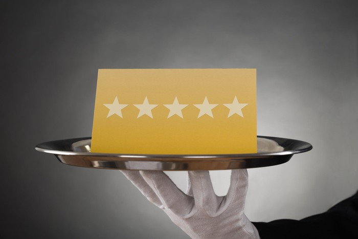 A butler holds a tray with a card displaying five stars in a row.