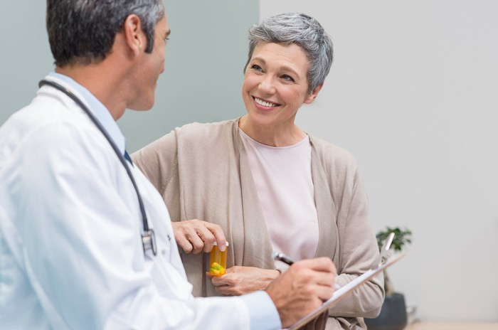 A senior woman discusses her prescription with her doctor.
