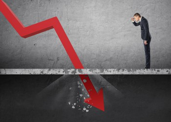 Businessman looking down at the falling red arrow breaking through floor