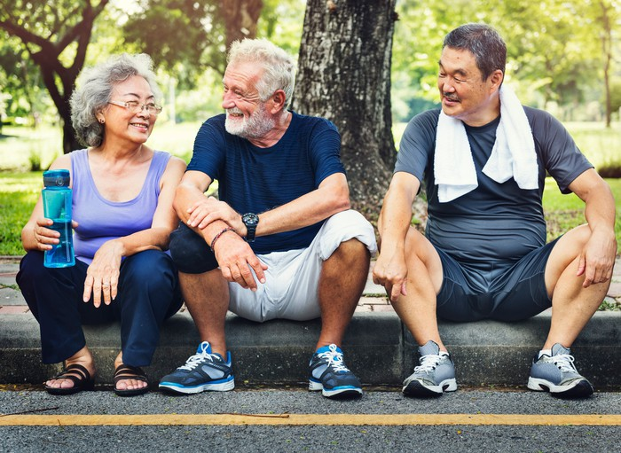Three people who have been working out sit on a curb.