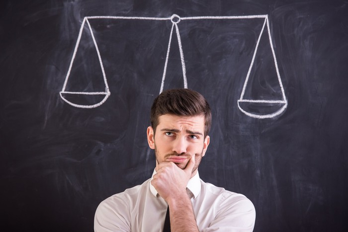Man thinking with hand on chin in front of chalkboard drawing of scales