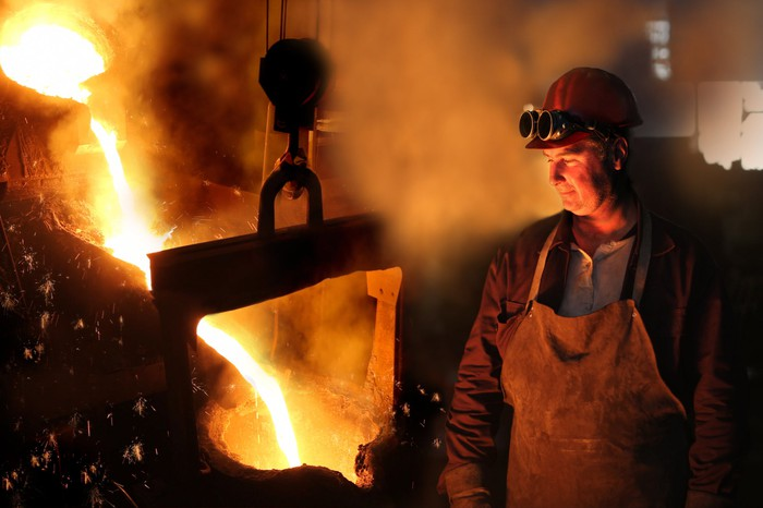 A steel worker looks on as iron is melted.