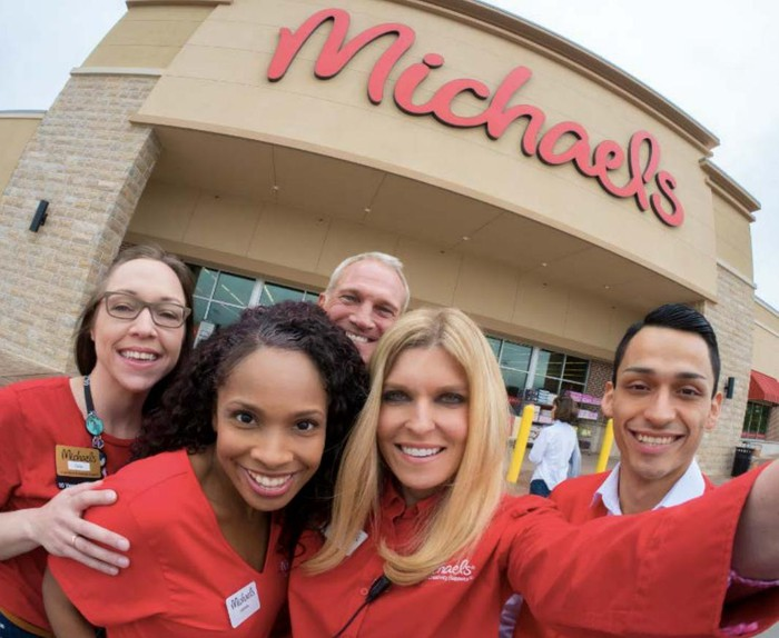 Five smiling Michaels employees taking a selfie under their store's company logo.