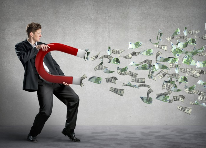 Man wearing suit holding giant red magnet with cash flowing toward the magnet