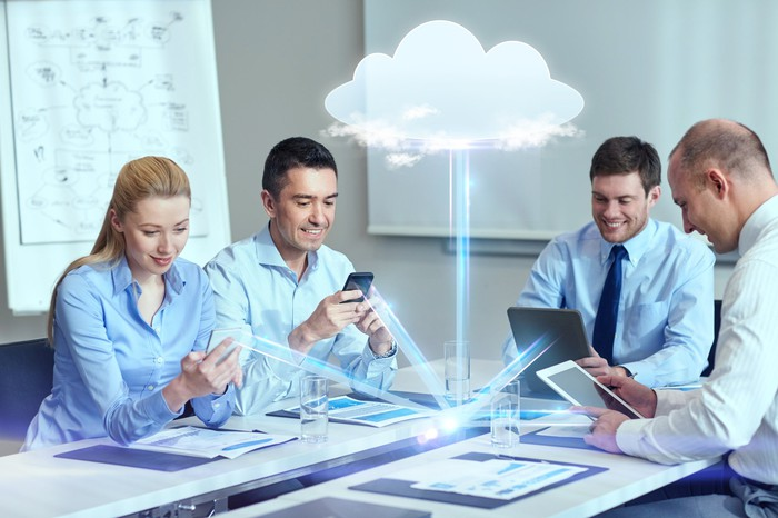 A group of business people gather data from the cloud.