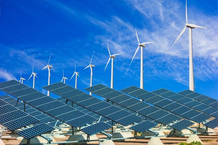 wind turbines and solar panels underneath blue skies