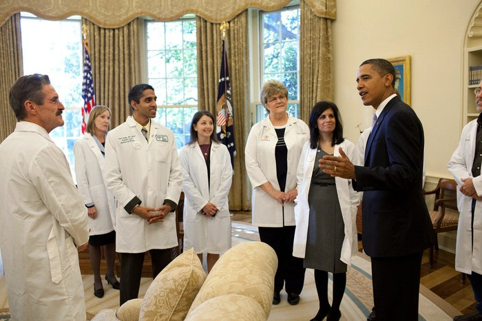 Former President Barack Obama having a discussion with doctors in the White House.