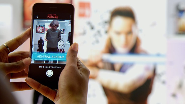 A hand holding a smartphone displaying Disney's Star Wars augmented reality app