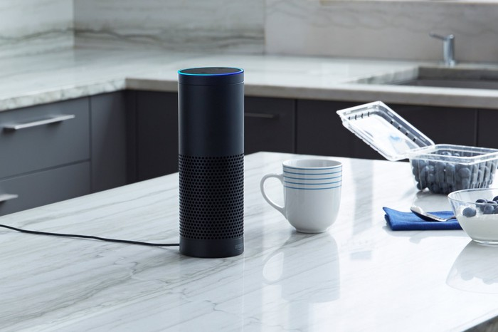 Amazon Echo on a kitchen counter, near a bowl, a box of blueberries, and a cup.