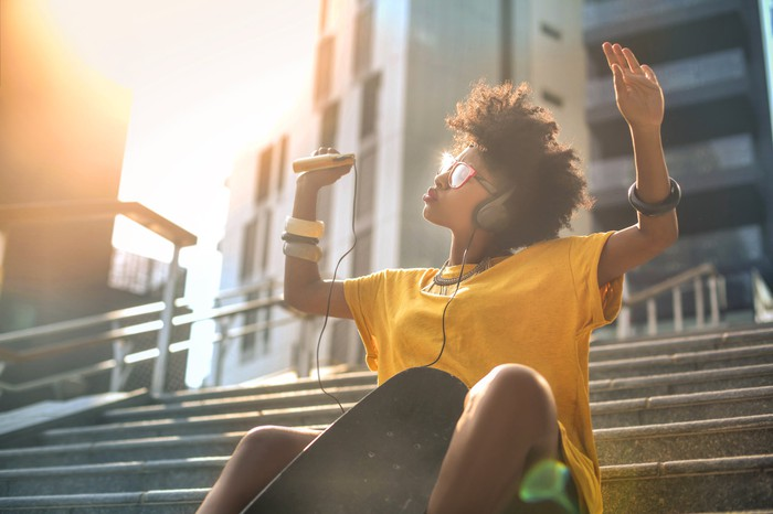 A woman in a yellow shirt sits outside on a flight of steps, raising her arms in the air as she listens to music.