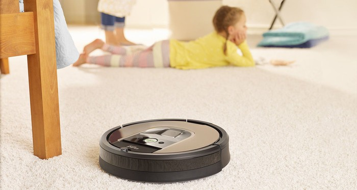 An iRobot Roomba vacuum sits on a carpeted floor next to a wooden chair, with a child lying on the floor in the background.