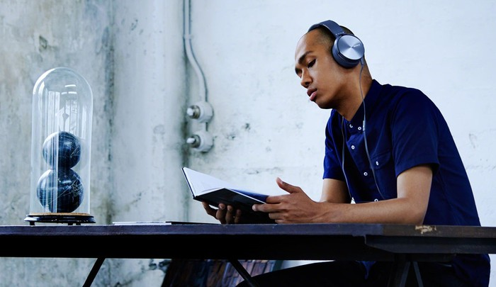 A man wearing Sony headphones sits reading at a table