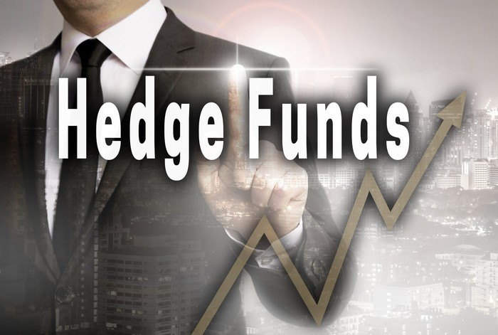 """Businessman standing in front of the words """"hedge funds."""""""