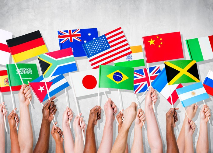 Hands holding flags of different countries.