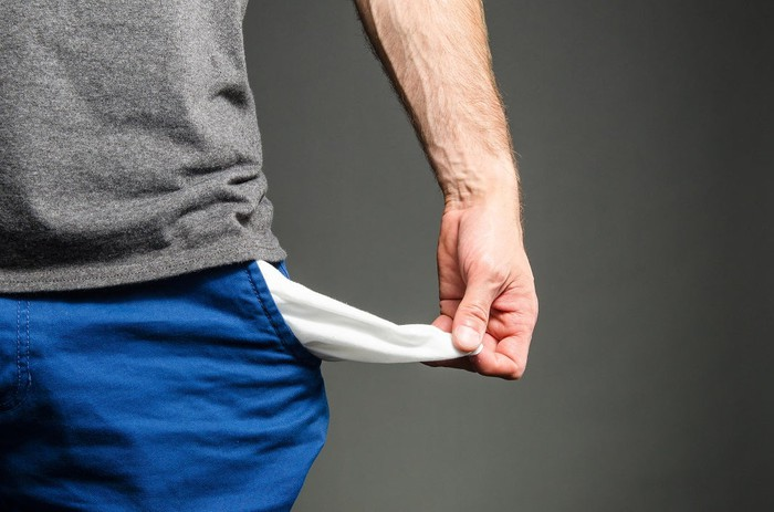 Man holding out empty pocket.