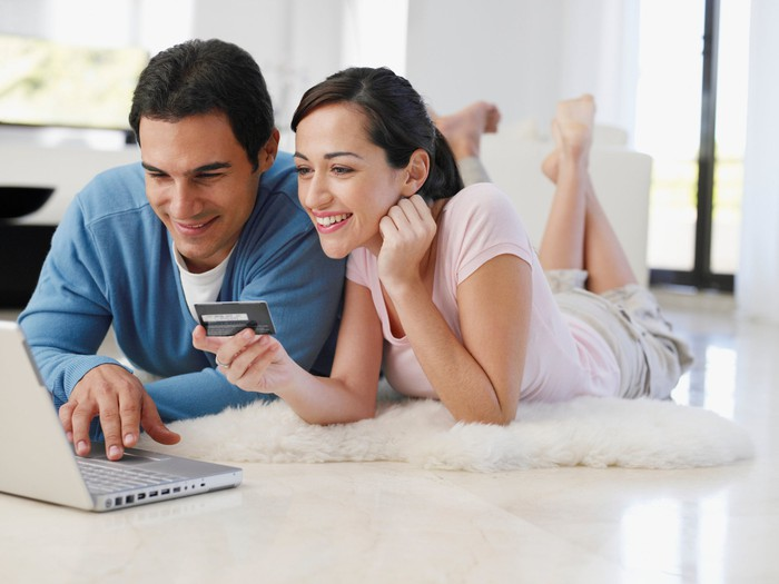 Couple laying on the floor with a laptop, woman is holding a credit card.