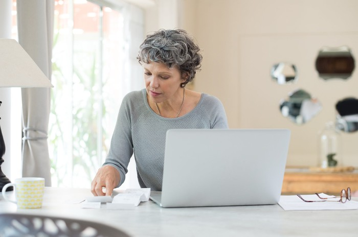 senior woman sitting at table in front of computer looking at receipts