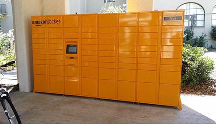 Picture of bright orange Amazon locker in a commercial shopping center courtyard.