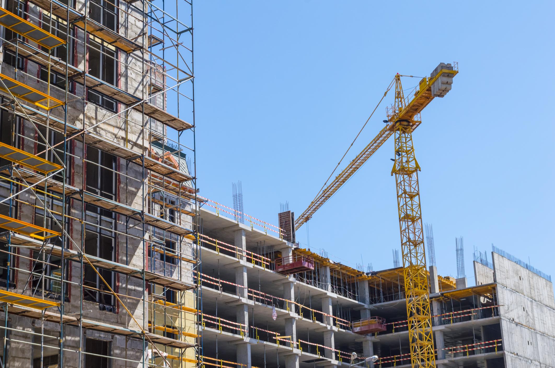 A giant crane building a large commercial building.